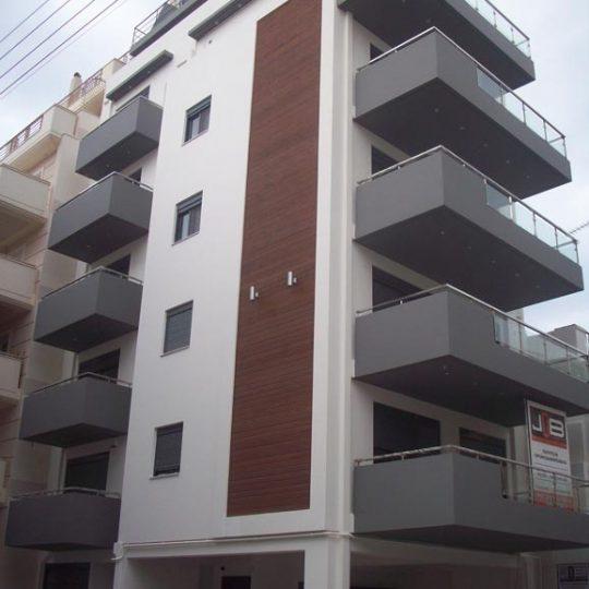 Πολυκατοικία με διακόσμηση από ξύλο ιρόκο και γκρι κάγκελα αλουμινίου και γυαλιού