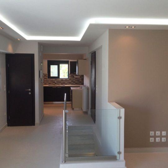 Κουζίνα μεζονέτας με κρυφό φωτισμό και κάγκελα από αλουμίνιο και γυαλί