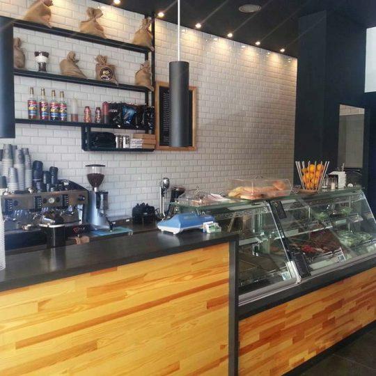 Ανακαίνιση καταστήματος καφέ και διακόσμηση με μεταλλίκη κατασκευή ραφιών, μασίφ επένδυση ξύλου, δάπεδο τεχνογρανίτη και επένδυση τοίχου στο χώρο παρασκευής με λευκό πλακάκι τουβλάκι